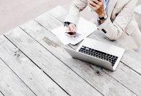 Mujer de negocios usando teléfono inteligente y portátil mientras está sentada en la mesa de madera - foto de stock