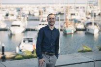 Uomo d'affari sorridente in piedi di fronte al porto — Foto stock