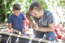 Отец и сын вместе строят песочницу в саду — стоковое фото