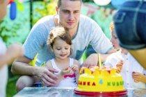 Niños celebrando fiesta de cumpleaños en el jardín con amigos y familiares - foto de stock