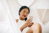 Frau liegt in Hängematte — Stockfoto
