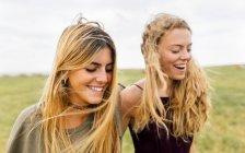 Due ragazze bionde adolescenti che passeggiano sulla costa — Foto stock