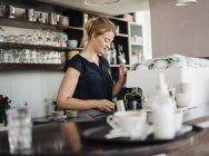 Женщина в кафе готовит молоко — стоковое фото