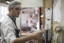 Butcher packing and labelling meat in butchery — Stock Photo
