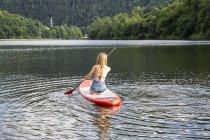Paddle femme d'embarquer dans le lac — Photo de stock