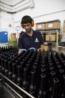 Man working in beer bottling plant — Stock Photo