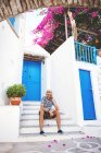 Greece, Amorgos island, young man sitting in on step and talking on cell phone — Stock Photo