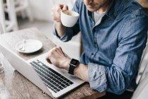 Hombre bebiendo café mientras trabaja en el ordenador portátil - foto de stock