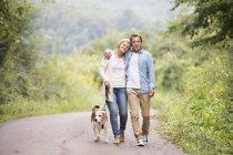 Coppia anziana in passeggiata con cane nella natura — Foto stock