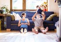 Отец и беременная мать играют с сыном дома — стоковое фото