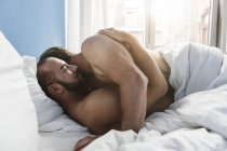 Gay couple embracing in bed — Stock Photo