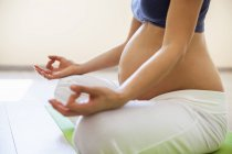Yoga prenatal, mujer meditando en posición de loto - foto de stock