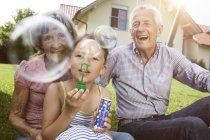 Großeltern und Enkelin im Garten pusten Seifenblasen — Stockfoto