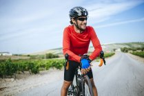 Smiling Cyclist man with bicycle standing on the road — Stock Photo