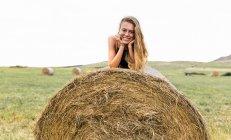 Portrait of smiling blond teenage girl lying on straw bale — Stock Photo
