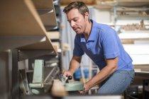 Человек, работающий на фиксатор инструмента в мастерской — стоковое фото