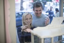 Lächelnd junges Paar auf der Suche im Schaufenster — Stockfoto
