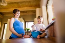 Little boy helping his pregnant mother in kitchen with electric whisker — Stock Photo