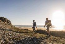 Francia, Bretaña, Finistere, Península de Crozon, pareja durante el senderismo en la playa - foto de stock
