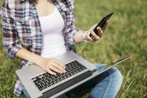 Молода жінка, сидячи на луг, використовуючи ноутбук і смартфон, частковим видом — стокове фото
