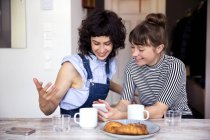 Two women at breakfast table looking together at smartphone — Stock Photo