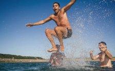 Три игривый друзья веселились в море — стоковое фото