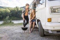 Couple ayant barbecue près de van — Photo de stock