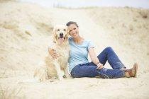 Усміхаючись молода жінка з собакою в піску — стокове фото