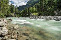 Вид на реку с камнями на берегу и мост на заднем плане — стоковое фото
