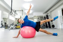 Senior man doing gymnastics on fitness ball in gym — Stock Photo