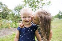 Mädchen küssen kleine Schwester im Garten — Stockfoto