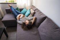 Женщина отдыхает на диване дома — стоковое фото