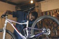 Meccanico in officina riparazione biciclette — Foto stock