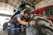 Mechanic changing tractor tire with colleague on background — Stock Photo