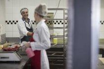 Personnes qui travaillent dans la boucherie parler et nettoyage — Photo de stock