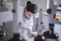 Young Woman taking notes in lab — Stock Photo