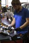 Механик исправлял электронные детали автомобиля в своей мастерской — стоковое фото