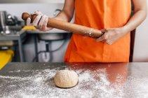 Pizzabäcker rollt Teig aus — Stockfoto