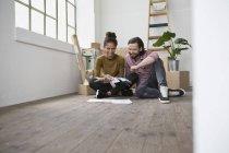 Coppia seduta sul pavimento del nuovo appartamento scegliendo tra campioni di colore — Foto stock