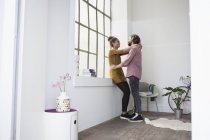 Young couple embracing in new flat — Stock Photo