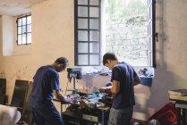 Два фальшивомонетчиков, работает в мастерской — стоковое фото