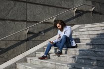 Businessman using cell phone on stairs — Stock Photo