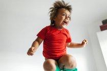 Niño saltando en cama - foto de stock