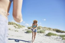 Молода жінка на пляжі, пограти в пляжний волейбол — стокове фото