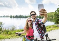 Young couple taking selfie on bicycle trip — Stock Photo