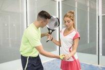 Man teaching woman in paddle tennis — Stock Photo