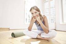 Женщина-йога, сидящая на полу в студии йоги — стоковое фото
