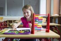 Smiling schoolgirl sitting at desk in her class — Stock Photo