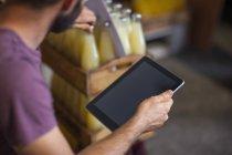 Mann mit Tablet kontrolliert Vorrat an Saftflaschen in Lagerhalle — Stockfoto
