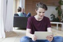 Adolescent souriant utilisant une tablette dans le salon avec les parents en arrière-plan — Photo de stock